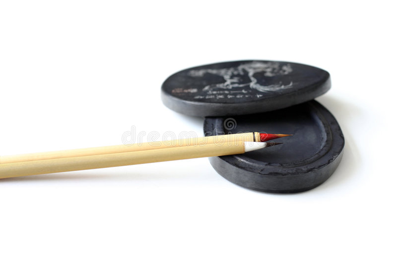 Chinese calligraphy brushes. A pair of two slim antique bamboo made chinese calligraphy or paint brushes, arranged neatly on an old black ink stone for grinding royalty free stock photography