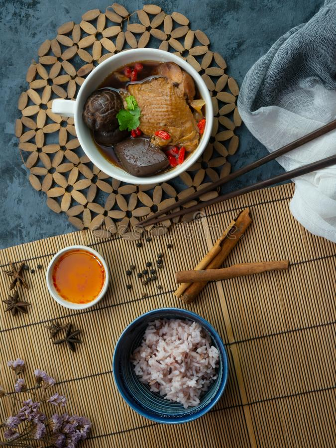 Chinese chicken soup in a white cup, decorated with Chinese shiitake mushrooms, goji berries, chicken blood and coriander leaves. royalty free stock photos