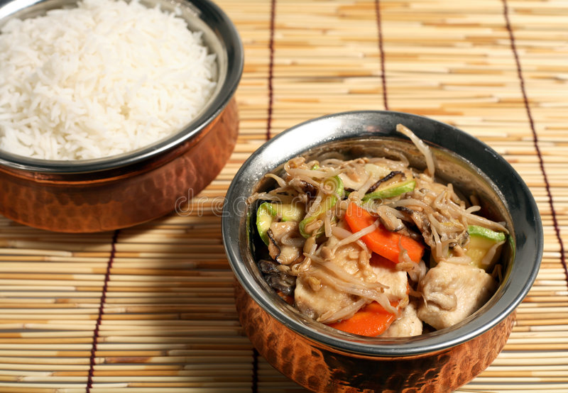 Chinese chicken stir-fry food. Seving bowl of chinese chicken stir-fry, with a bowl of white rice behind royalty free stock photos