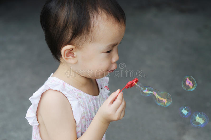 Chinese child blowing bubbles stock image