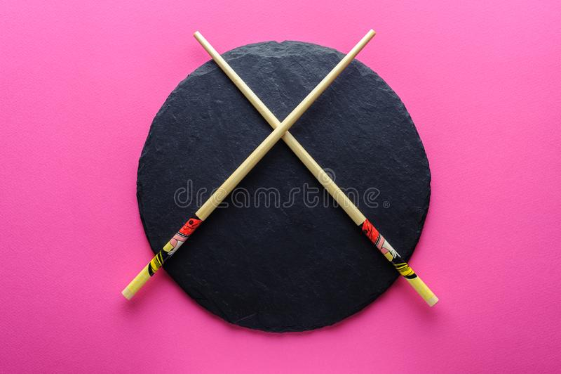 Chinese chopsticks on an empty slate plate.  stock photo