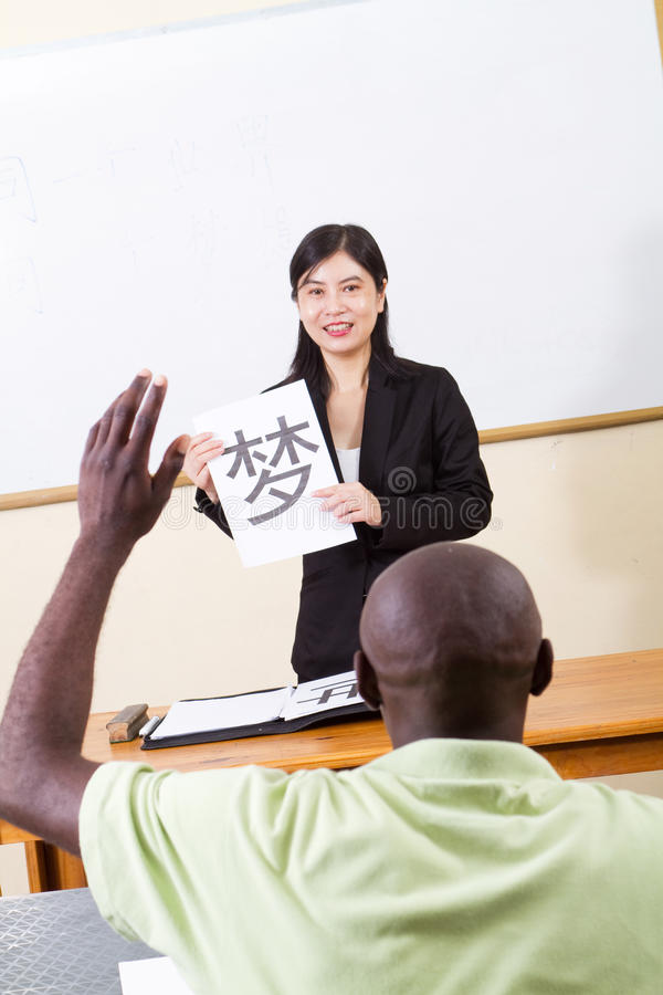 Chinese class. An african adult student raising his hand to ask the young chinese teacher a question in chinese class royalty free stock photo