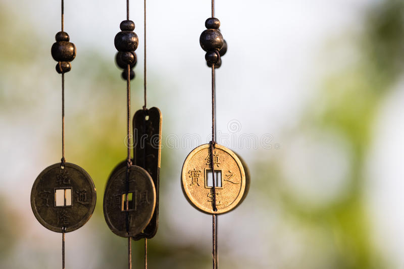 Chinese coins chime. Antique Chinese coins hanged outside the house as wind chimes for protection and good luck stock photos