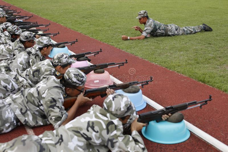 Chinese collage student military training. Freshmen from Zhejiang University practise aiming under instruction of a sergeant during the mandated military stock image