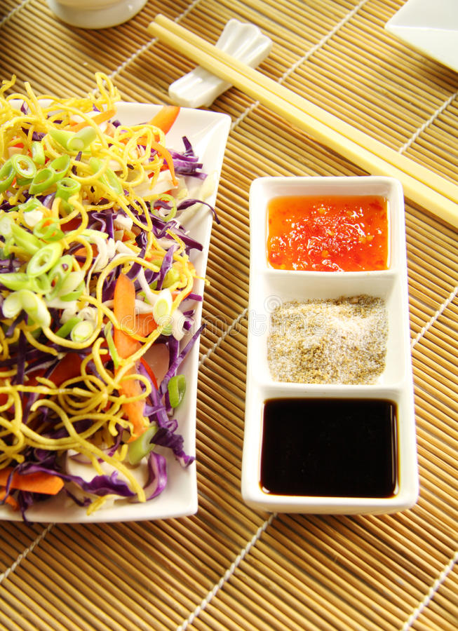 Chinese Condiments. Consisting of soy sauce, chinese spicy salt and sweet chilli sauce with a noodle salad royalty free stock image