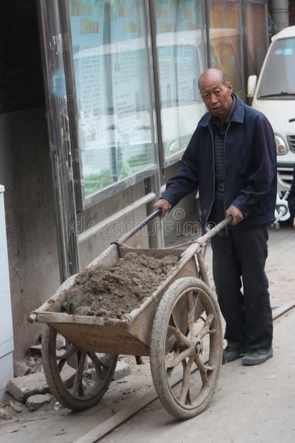 Chinese construction worker carries a wheelbarrow with soil, an elderly man, hard work stock photography
