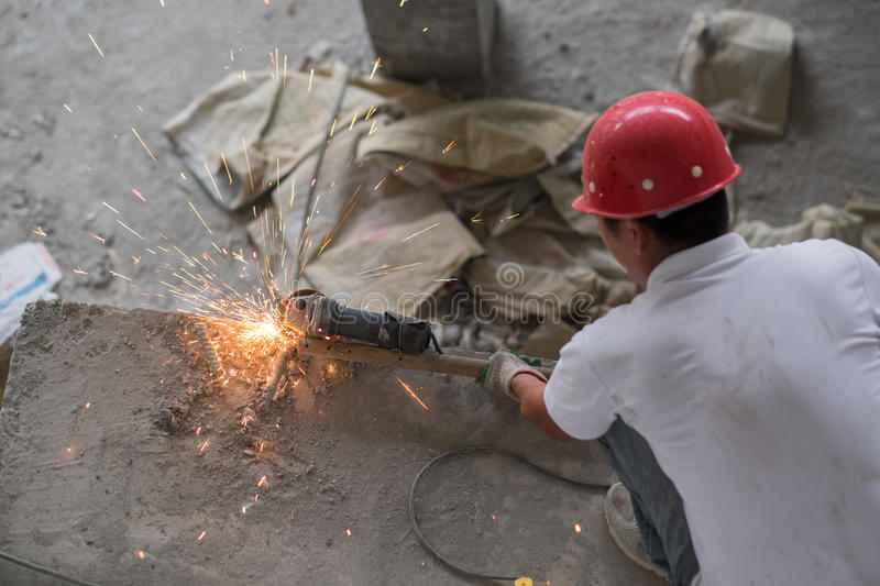 Chinese Construction Worker Cutting Metal Rebar. An asian construction worker is cutting metal rebar while squatting on a concrete pillar. He is wearing a red stock photos