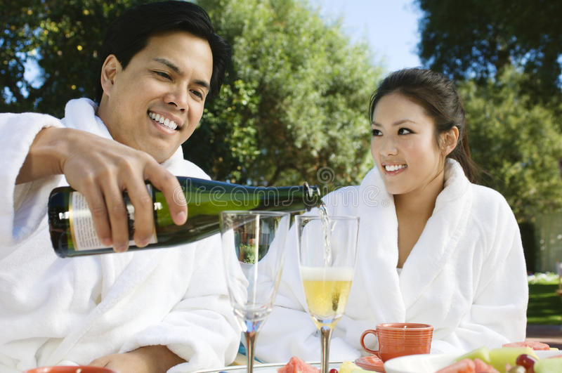 Chinese Couple Wearing Bathrobes Drinking Champagne royalty free stock image