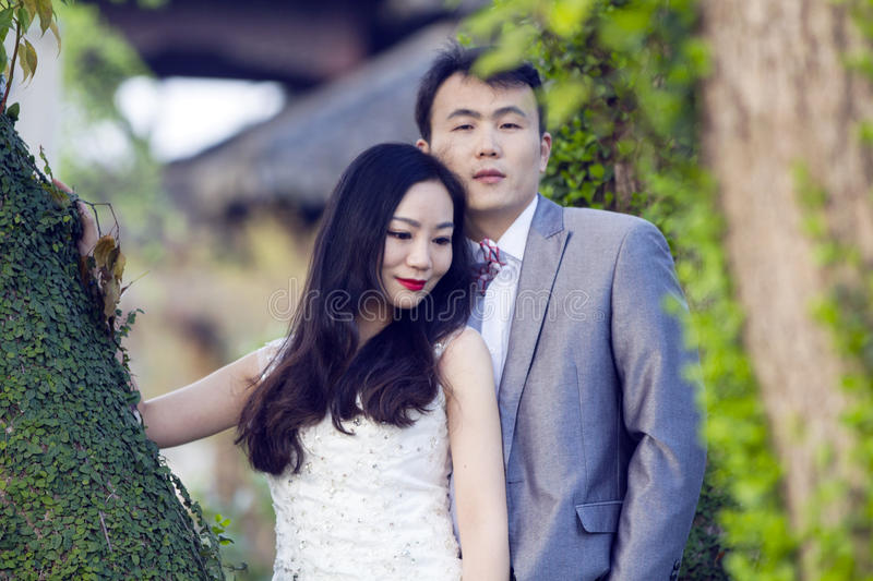 Chinese couple wedding portraint in front of Old trees and old building. White flowers , canola,cauliflower, bride wear a white crown on her head, with bridal royalty free stock photos