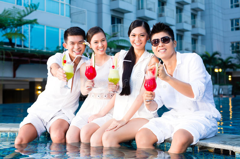 Chinese couples drinking cocktails in hotel pool bar. Two young and handsome Asian Chinese couples or friends drinking cocktails in a luxurious and fancy hotel stock photography
