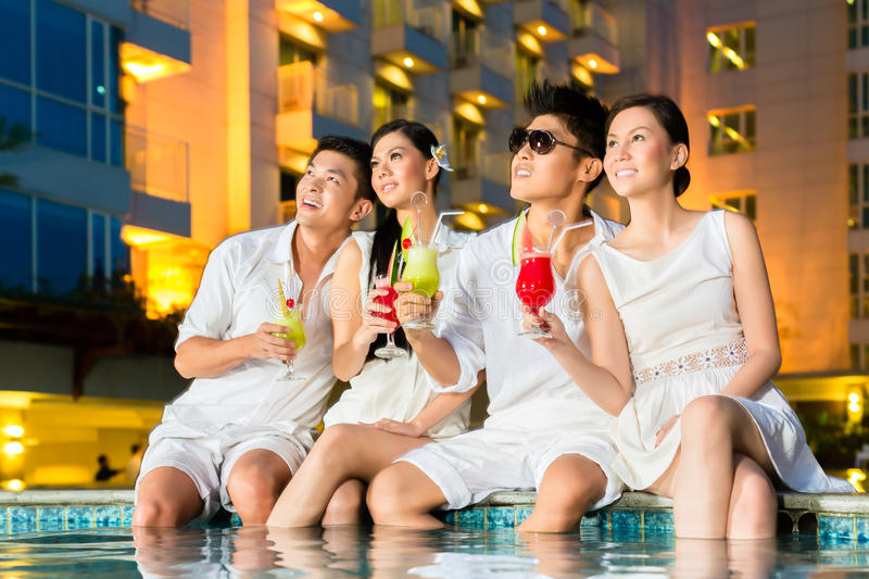 Chinese couples drinking cocktails in hotel pool bar. Two young and handsome Asian Chinese couples or friends drinking cocktails in a luxurious and fancy hotel stock photo