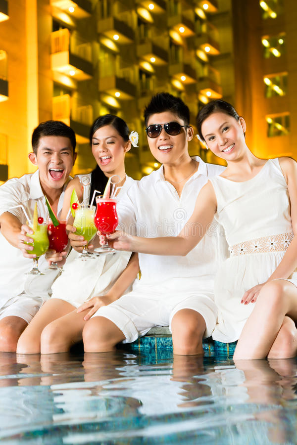 Chinese couples drinking cocktails in hotel pool bar. Two young and handsome Asian Chinese couples or friends drinking cocktails in a luxurious and fancy hotel royalty free stock image