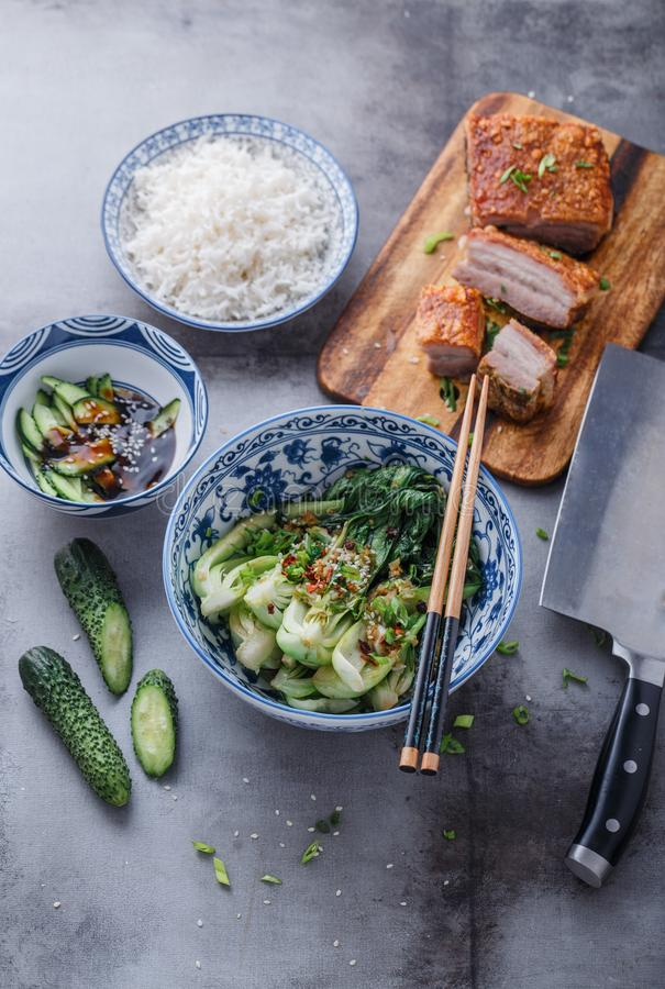 Chinese cuisine stir-fried bok choy and crispy pork belly.  royalty free stock image