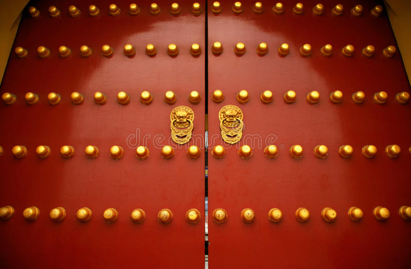 Chinese culture. Gate of the Forbidden City in Beijing. The big gold buttons are doornails. There are NINE mounted in the gate both horizontal and perpendicular royalty free stock photo