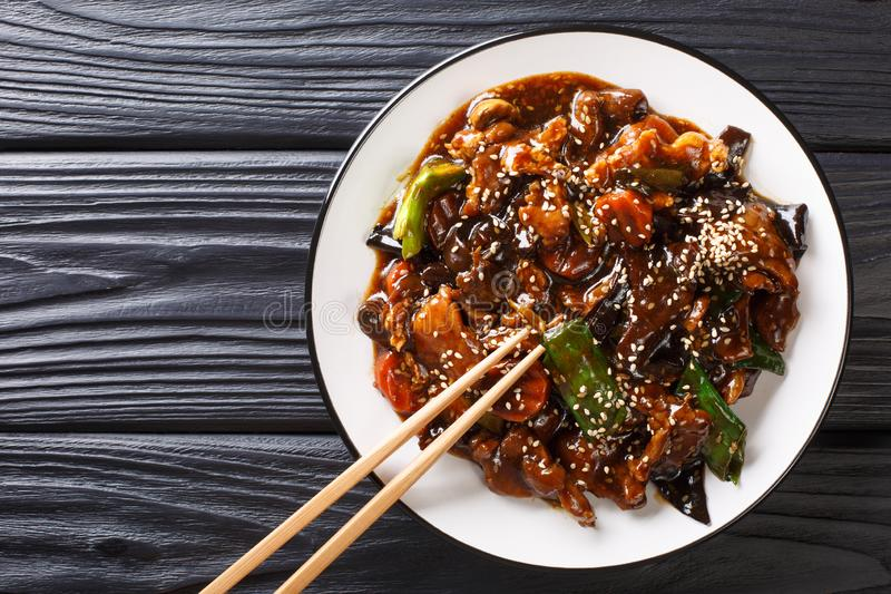 Chinese delicious stir fry pork with mun mushrooms and vegetables close-up on a plate. Horizontal top view royalty free stock photography