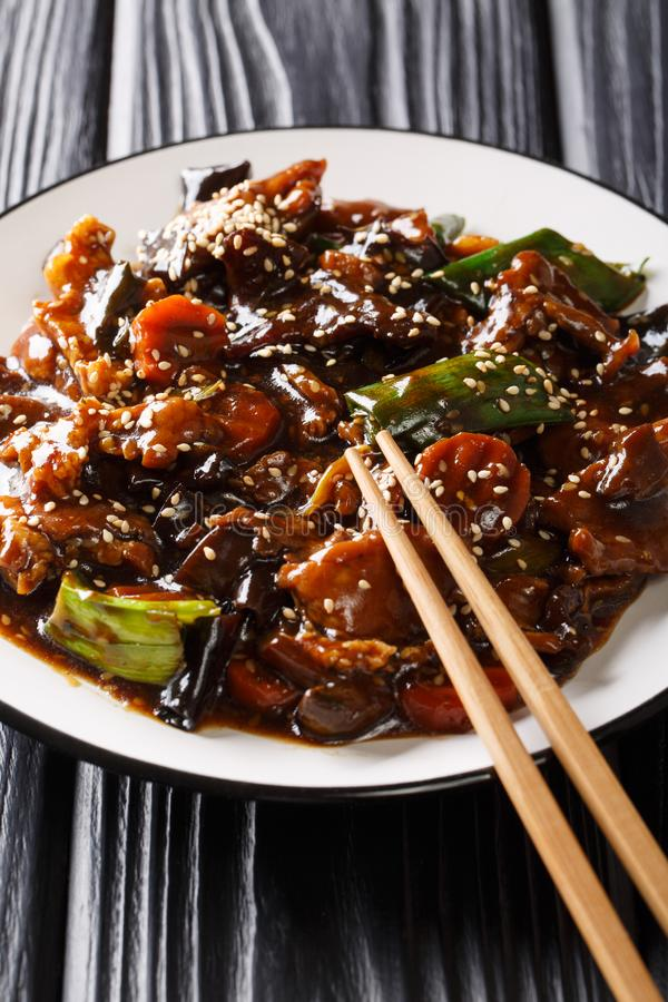 Chinese delicious stir fry pork with mun mushrooms and vegetables close-up on a plate. vertical. Chinese delicious stir fry pork with mun mushrooms and royalty free stock photography