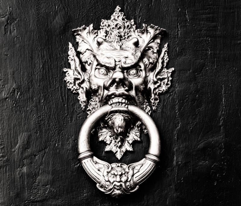 Chinese demon golden door handle - knocker in a black and white wooden door royalty free stock image