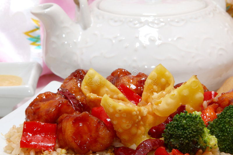 Chinese Dinner. General Tso, fried rice, crab rangoon in kitchen or restaurant setting royalty free stock photos