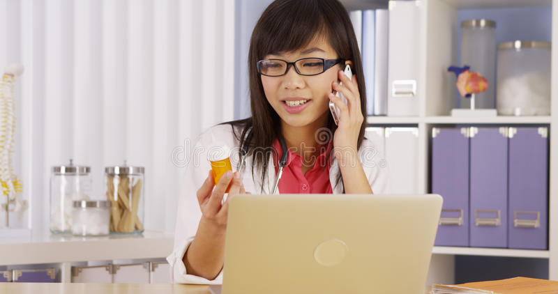 Chinese doctor talking on phone about prescription. Chinese doctor talking on phone with prescription stock photography