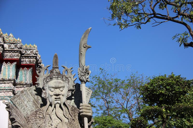 Chinese Stone Doll With Sword And Leaves. Chinese ballast doll in wat pho Temple Bangkok Thailand with multicolor ceramic  and  blue sky in summertime stock image