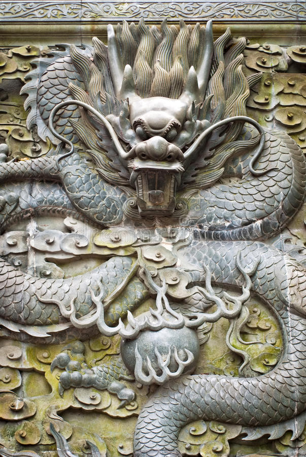 Chinese dragon. Stone carving chinese dragon on wall with open mouth, wave claw and warping body.Showing power and honour stock image