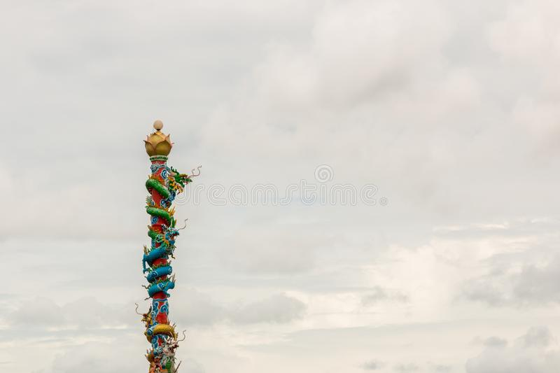 Chinese dragon statue on red pillars, very cloudy.  stock photo