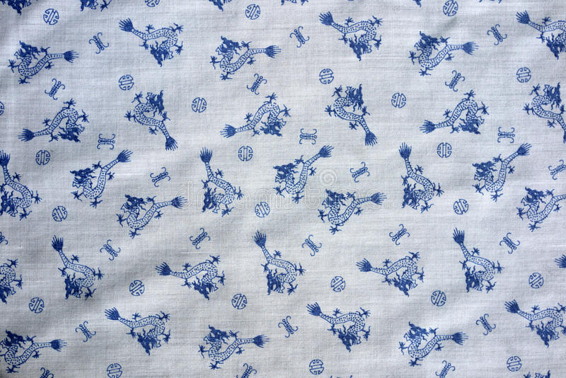 Chinese dragon and symbols Vintage real fabric 1970s nylon white and blue. Pattern, material close up, repeat pattern for clothes, 1960s, shirt fabric old style royalty free stock image