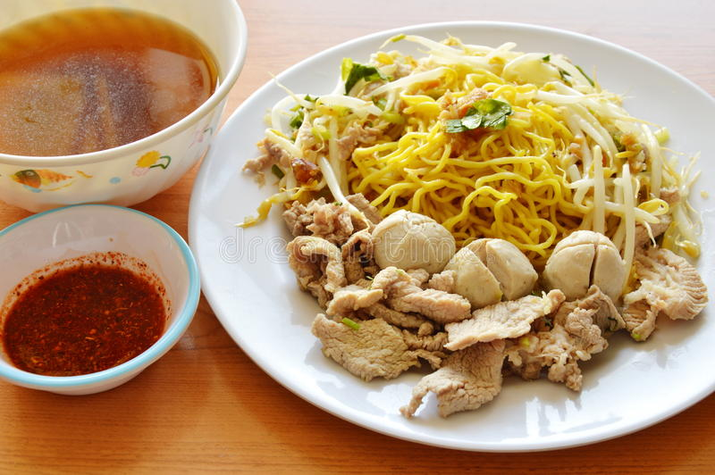 Chinese egg noodle topping boiled pork and soup with cayenne pepper sauce. On desk stock photography