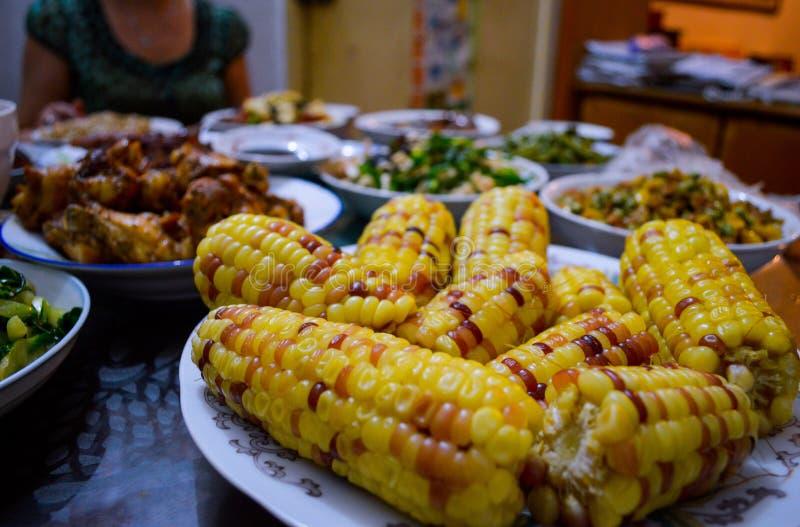 Chinese Familiemaaltijd op Lijst met Graan op Maïskolven bij voorzijde stock afbeeldingen