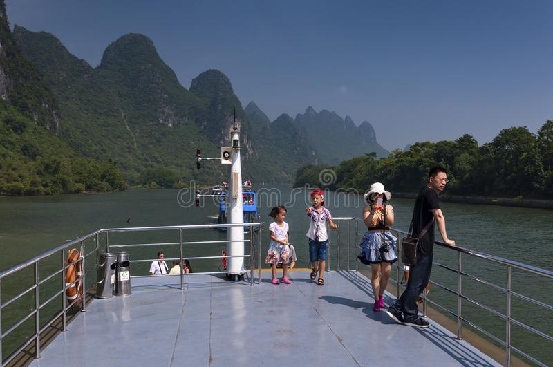 Chinese family in a boat cruising in the Li River and looking at the the tall limestone mountains near Yangshuo in China royalty free stock photos