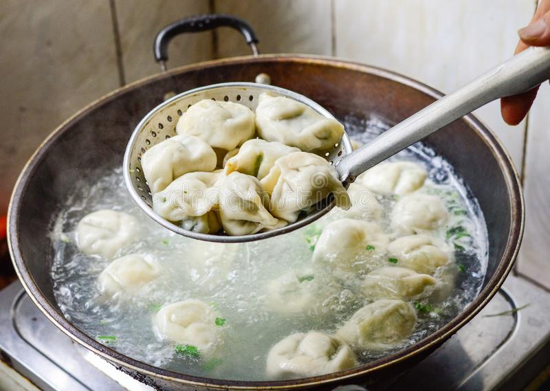 Chinese Family Cooking Boiled Dumplings in Wok. Chinese Family Cooking Boiled Dumplings. The dumplings are picked up from the wok stock photos