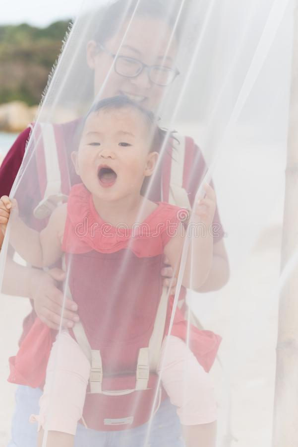 Chinese mom and little girl in baby carrier vacation on beach stock images