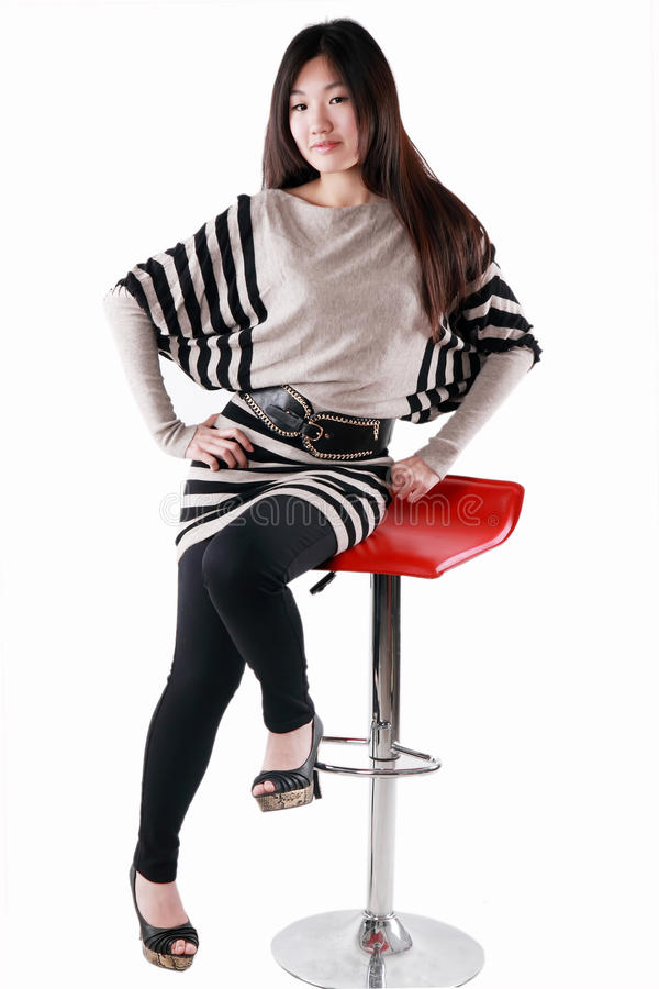 Chinese fashion model sitting a chair