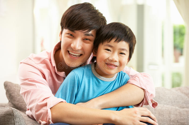 Chinese Father And Son Relaxing On Sofa At Home stock image
