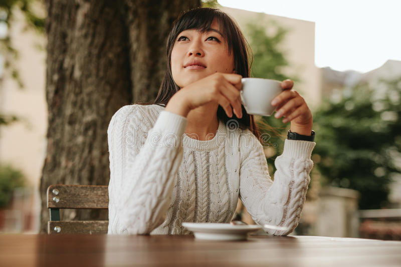 Chinese female having coffee at cafe stock photo
