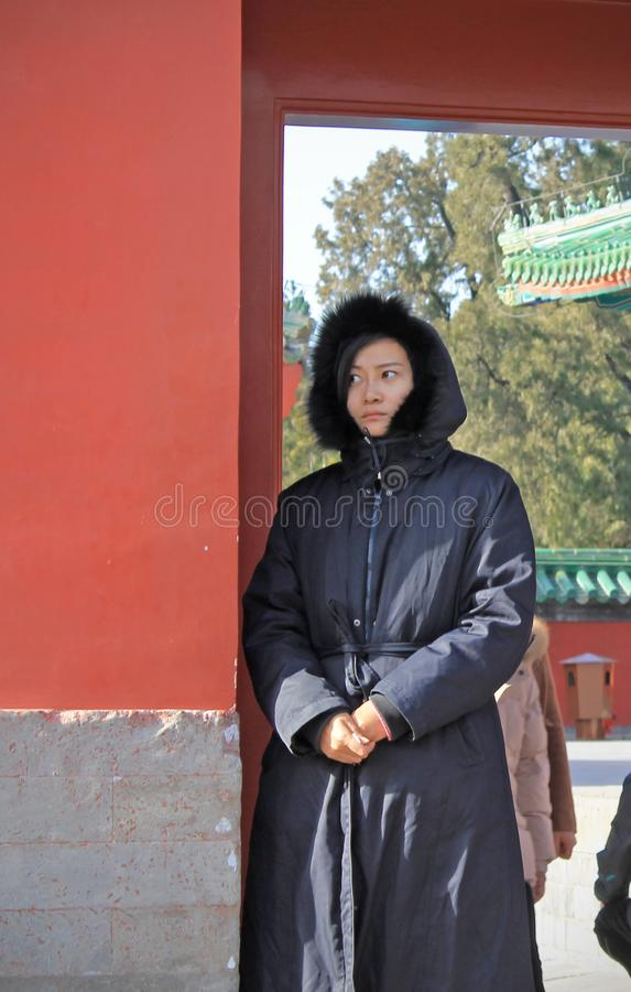 Chinese woman by the red wall in the temple royalty free stock images