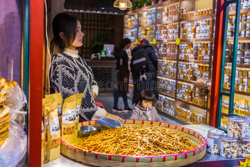 Chinese female snack seller waits for her customer at her snack stock images
