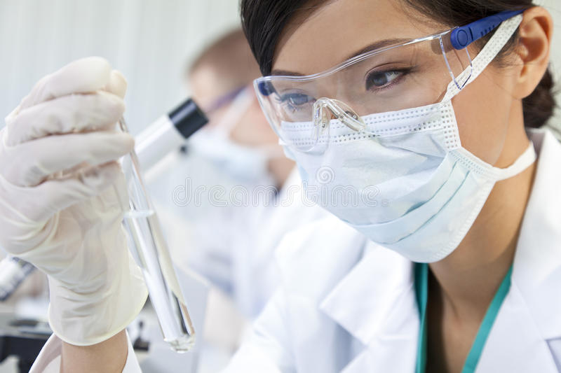 Chinese Female Woman Scientist With In Laboratory. A Chinese Asian female medical or scientific researcher or doctor using looking at a test tube of clear liquid stock image