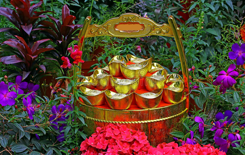 Chinese feng shui gold ingots and wealth pot. Traditional chinese feng shui gold ingots and wealth pot displayed in a garden during chinese new year royalty free stock photo