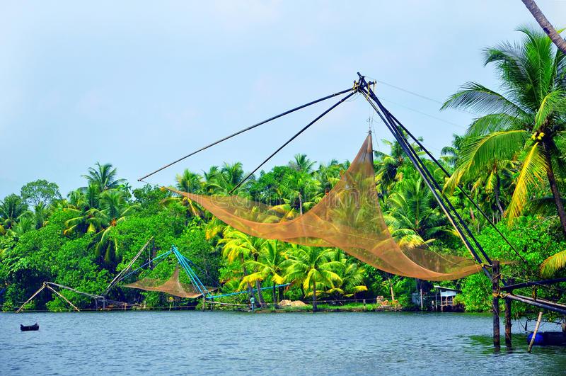 Chinese fishing nets at cochin, kerala, india. Coastal view of cochin, kerala, india with chinese fishing nets, coconut and mango trees in the background royalty free stock photos
