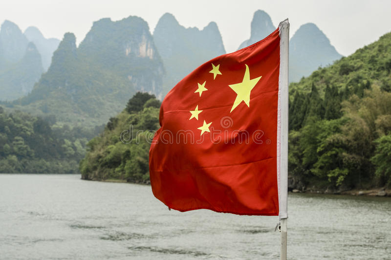 Chinese flag over the Li-River. Chinese flag blowing in the wind in front of the mountains around the Li-River near by Longsheng stock images