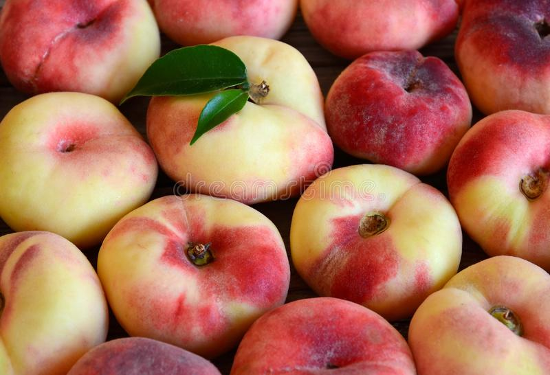 Chinese flat donut peaches also known as Saturn donut, Doughnut peach,Paraguayo as a background.Healthy eating or diet concept. Selective focus royalty free stock images