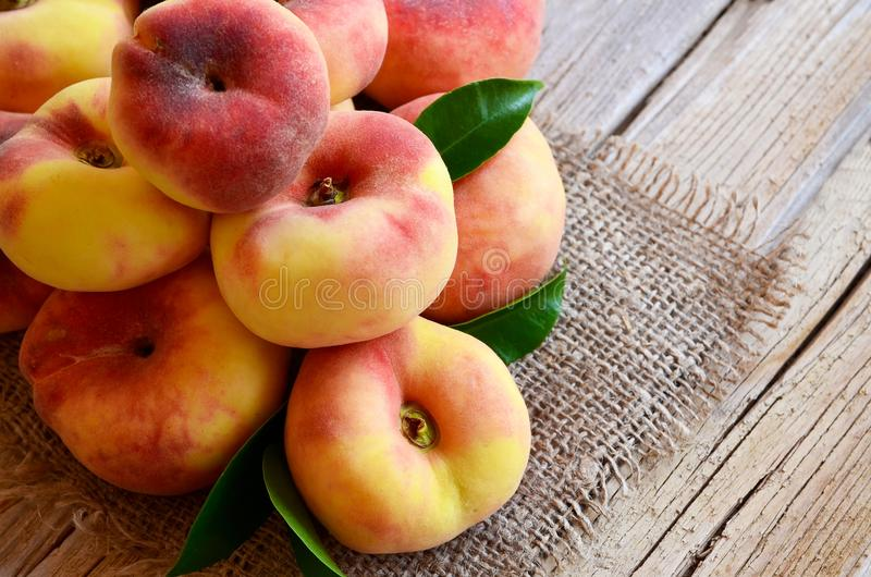 Chinese flat donut peaches with leaves on on old wooden table also known as Saturn donut, Doughnut peach, Paraguayo.Healthy eating. Or diet concept.Selective royalty free stock photos