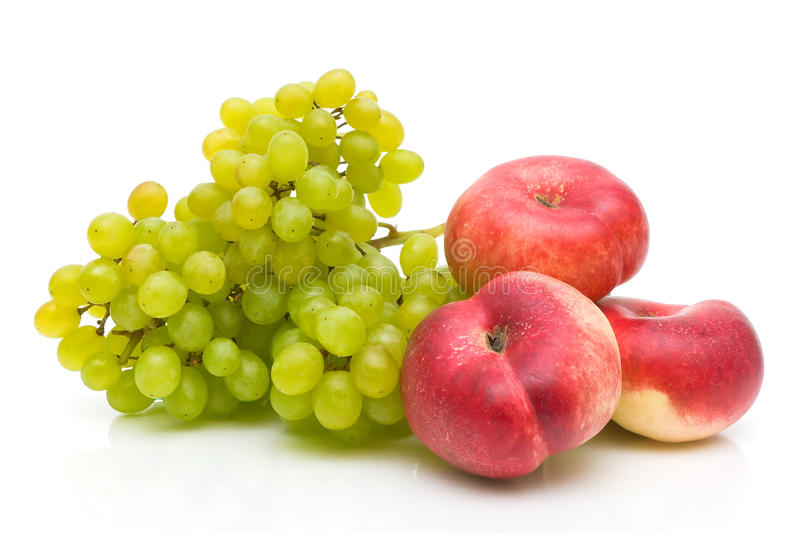 Chinese flat peaches and green grapes on white stock photo