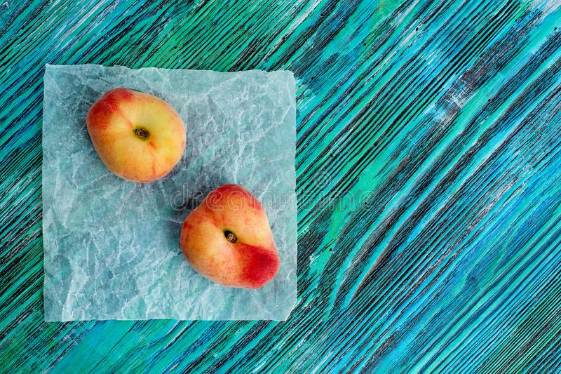 Chinese flat peaches on rustic colorful background with copy space. Flat lay background. stock photos