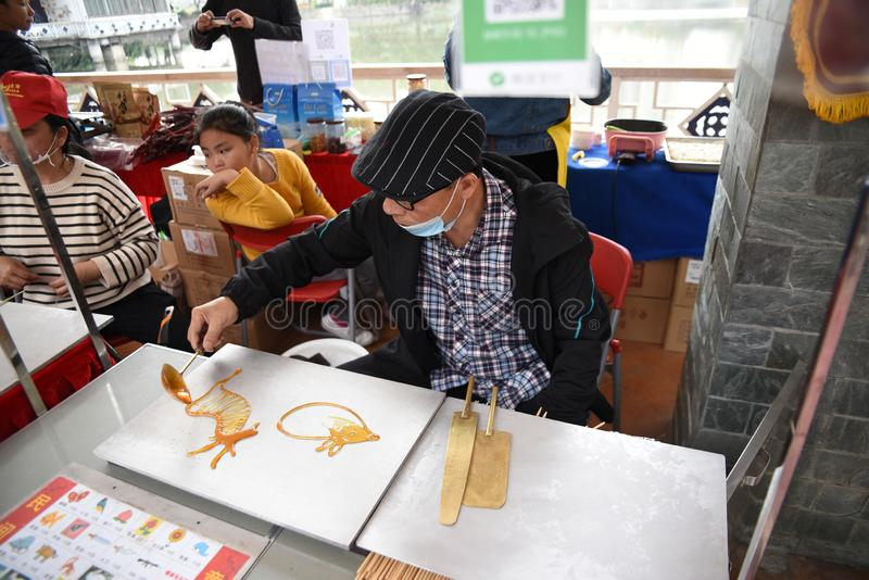 Chinese folk craftsman who is making sugar paintings. Chinese sugar painting is an ancient folk art with a history of thousands of years royalty free stock images