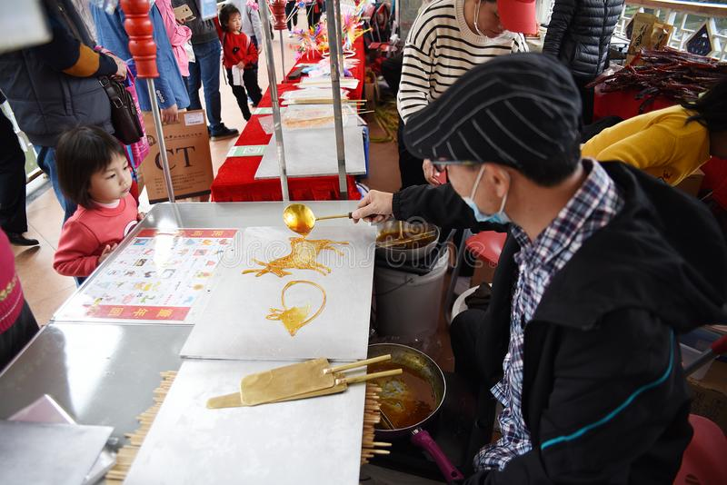 Chinese folk craftsman who is making sugar paintings. Chinese sugar painting is an ancient folk art with a history of thousands of years stock image
