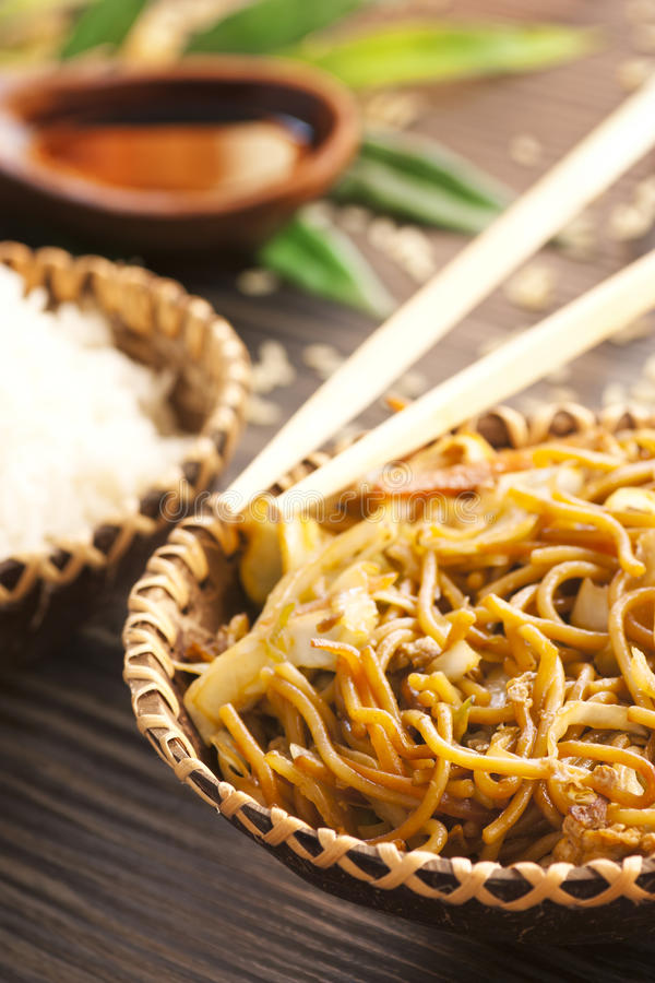 Chinese food. Egg noodles with chicken and vegetables, steamed rice and soy sauce on bamboo leaf royalty free stock photography