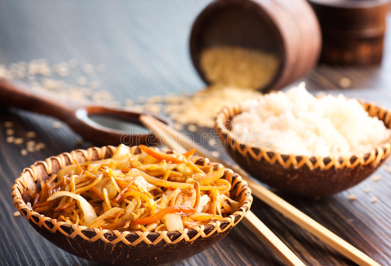 Chinese food. Egg noodles with chicken and vegetables, steamed rice and soy sauce stock image