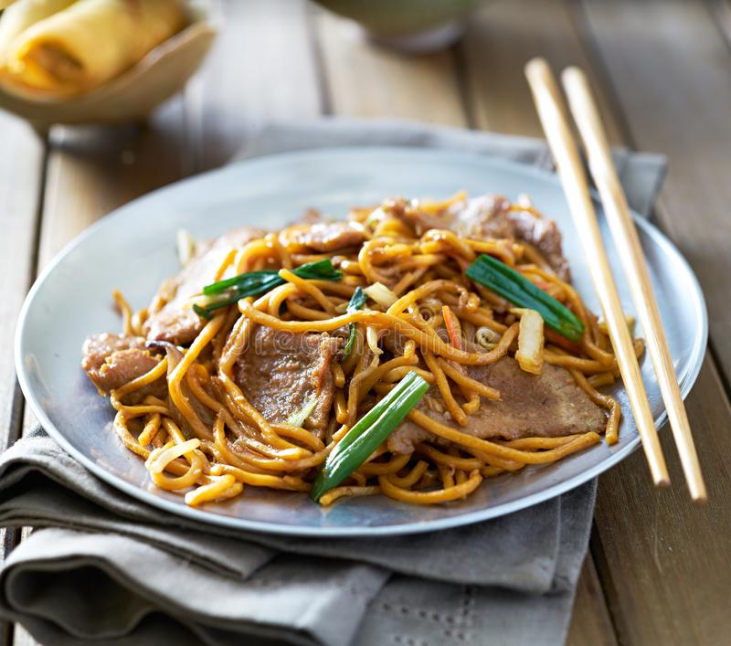 Chinese food - beef lo mein on a plate with chopsticks stock image